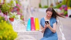 Forme a la muchacha feliz con los bolsos después de selfie que toma que hace compras en café al aire libre Venta, consumerismo y  almacen de metraje de vídeo