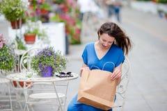 Forme a la muchacha feliz con los bolsos después de café de consumición que hace compras en café al aire libre Venta, consumerism Imagen de archivo