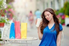Forme a la muchacha feliz con los bolsos después de café de consumición que hace compras en café al aire libre Venta, consumerism Imagen de archivo libre de regalías