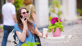Forme a la muchacha feliz que habla por el teléfono después de café de consumición que hace compras en café al aire libre Venta,  almacen de video