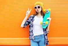 Forme a la muchacha fresca con el monopatín que se divierte sobre naranja colorida Fotos de archivo