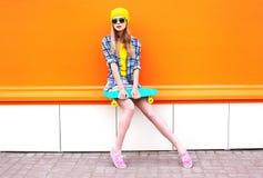 Forme a la muchacha fresca con el monopatín sobre naranja colorida Fotos de archivo libres de regalías