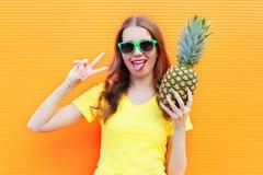 Forme a la muchacha fresca en gafas de sol con la piña que se divierte sobre naranja colorida Fotos de archivo