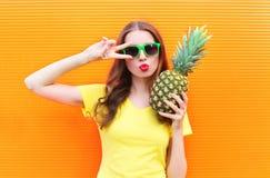 Forme a la muchacha fresca en gafas de sol con la piña sobre naranja colorida Foto de archivo libre de regalías