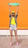 Forme a la muchacha fresca en las gafas de sol y la ropa colorida, monopatín Fotos de archivo libres de regalías