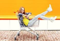Forme a la muchacha fresca que se divierte que se sienta en carro de la carretilla de las compras Imagen de archivo