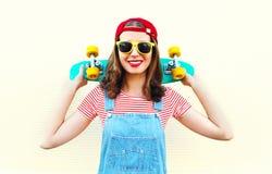 Forme a la muchacha fresca que sonríe con el monopatín sobre blanco Fotografía de archivo libre de regalías