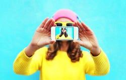 Forme a la muchacha fresca que toma el autorretrato de la foto en smartphone sobre el fondo blanco que lleva la ropa y las gafas  Imagenes de archivo
