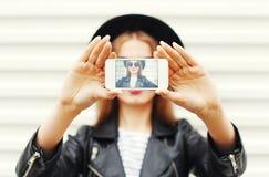 Forme a la muchacha fresca que toma el autorretrato de la imagen en smartphone sobre blanco Imagen de archivo libre de regalías