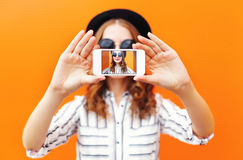 Forme a la muchacha fresca que toma el autorretrato de la imagen en smartphone sobre naranja colorida Imagen de archivo libre de regalías
