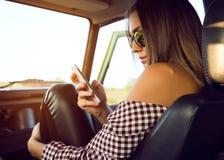 Forme a la muchacha hermosa que usa su teléfono móvil en el coche Fotos de archivo