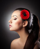 Forme a la muchacha morena con la flor aislada en fondo texturizado Fotos de archivo