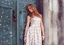 Forme a la muchacha pelirroja que se coloca cerca de una pared azul Fotografía de archivo libre de regalías