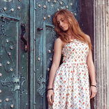 Forme a la muchacha pelirroja que se coloca cerca de una pared azul Imagenes de archivo