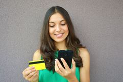 Forme a la muchacha que compra en línea con la tarjeta elegante del teléfono y de crédito aislada en el fondo violeta Fotos de archivo libres de regalías