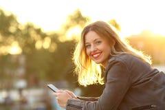 Forme a la muchacha que mira la cámara que sostiene un teléfono elegante Foto de archivo libre de regalías