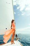 Forme a la muchacha que navega en el mar con luz del sol del cielo azul Fotos de archivo libres de regalías