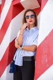 Forme a la muchacha que presenta sobre fondo rayado blanco rojo de la pared La mujer de la belleza con los labios rosados constru Foto de archivo libre de regalías
