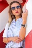 Forme a la muchacha que presenta sobre fondo rayado blanco rojo de la pared La mujer de la belleza con los labios rosados constru Imagen de archivo