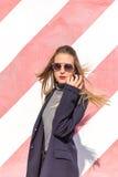 Forme a la muchacha que presenta sobre fondo rayado blanco rojo de la pared La mujer de la belleza con los labios rosados constru Imagen de archivo libre de regalías