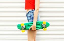 Forme a la muchacha que sostiene el monopatín en pantalones cortos del dril de algodón sobre blanco Fotografía de archivo