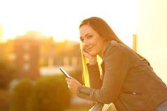 Forme a la muchacha que sostiene un teléfono que mira la cámara la puesta del sol Imagen de archivo