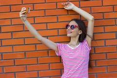 Forme a la muchacha que toma el autorretrato en smartphone en ciudad sobre fondo rojo de la pared de ladrillo Imágenes de archivo libres de regalías