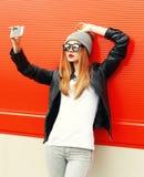 Forme a la muchacha que toma el autorretrato en smartphone en ciudad sobre rojo Imagen de archivo libre de regalías