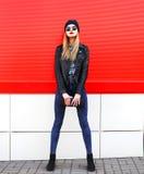 Forme a la muchacha rubia en estilo del negro de la roca con el embrague del bolso sobre rojo Imagenes de archivo