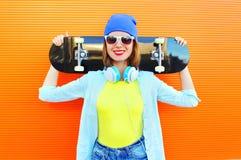 Forme a la muchacha sonriente bastante fresca con un monopatín en la ciudad sobre naranja colorida Fotos de archivo
