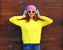 Forme a la muchacha sonriente bastante fresca que disfruta de escuchar la música en los auriculares que llevan el suéter hecho pu Foto de archivo