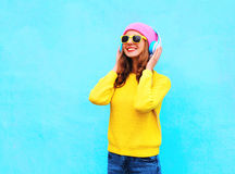 Forme a la muchacha sonriente bastante fresca que escucha la música en los auriculares que llevan las gafas de sol y el suéter ro Fotos de archivo libres de regalías