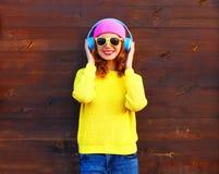 Forme a la muchacha sonriente bastante fresca que escucha la música en los auriculares que llevan un suéter hecho punto amarillo  Imágenes de archivo libres de regalías