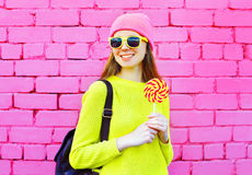 Forme a la muchacha sonriente del retrato con la piruleta sobre fondo colorido Fotografía de archivo libre de regalías
