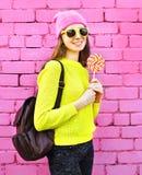 Forme a la muchacha sonriente del retrato con la piruleta sobre fondo colorido rosado Imágenes de archivo libres de regalías