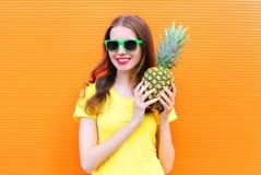 Forme a la muchacha sonriente fresca en gafas de sol con la piña sobre naranja colorida Fotos de archivo libres de regalías
