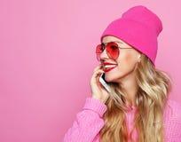 Forme a la muchacha sonriente fresca feliz que habla en smartphone en cl rosado Imágenes de archivo libres de regalías