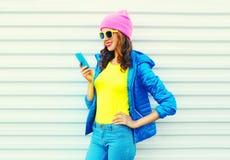 Forme a la muchacha sonriente fresca feliz que usa smartphone en ropa colorida sobre el fondo blanco las gafas de sol rosadas de  Fotos de archivo libres de regalías