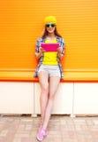 Forme a la muchacha sonriente fresca que usa la PC de la tableta sobre naranja colorida Imagen de archivo libre de regalías