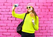 Forme a la muchacha sonriente que toma el retrato del selfie de la foto usando smartphone sobre colorido Imagen de archivo libre de regalías