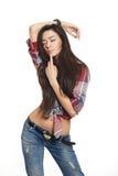 Forme a la muchacha triguena atractiva en pantalones vaqueros y camisa Fotos de archivo libres de regalías