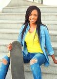 Forme a la mujer africana bastante joven con la sentada del monopatín Fotos de archivo libres de regalías