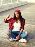 Forme a la mujer africana bastante joven que se divierte en ciudad imagen de archivo libre de regalías