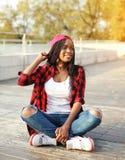 Forme a la mujer africana bastante joven que se divierte en parque de la ciudad Imagen de archivo