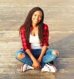Forme a la mujer africana bastante joven que se sienta en el parque de la ciudad, llevando una camisa a cuadros roja Fotografía de archivo libre de regalías