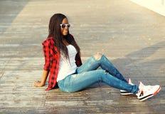 Forme a la mujer africana bastante joven que se sienta en parque de la ciudad Fotografía de archivo libre de regalías