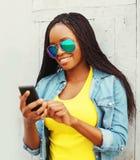 Forme a la mujer africana bastante sonriente que usa smartphone en ciudad Imágenes de archivo libres de regalías