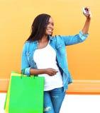 Forme a la mujer africana con los panieres que toman la foto del autorretrato en smartphone sobre fondo anaranjado Fotografía de archivo libre de regalías