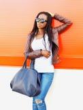 Forme a la mujer africana en gafas de sol con el bolso que presenta en la ciudad sobre rojo Foto de archivo