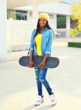 Forme a la mujer africana joven con el monopatín en ciudad Foto de archivo libre de regalías